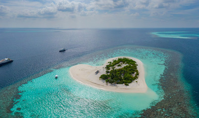 Aerial panoramic view on heart shaped tropical island in blue sea at Maldives background