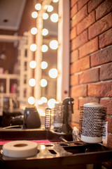 Round hairbrush and other tools in the beauty salon. Focus on the comb. Shallow depth of field
