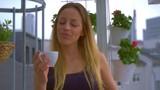 Woman on balcony is drinking coffee  - 246595030