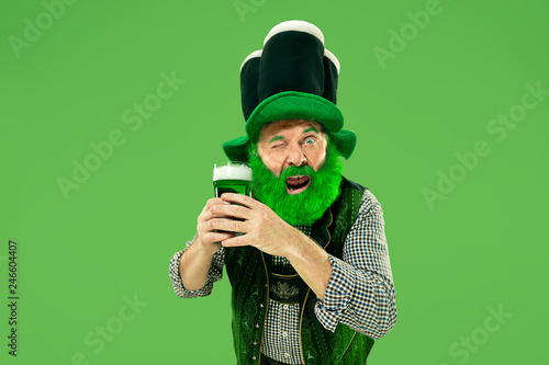 fototapeta na ścianę A smiling happy senior man in a leprechaun hat with green beer at studio. He celebrates St. Patrick's Day. The celebration, festive, beer, holiday, alcohol, party concept