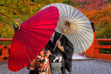 Couple with traditional japanese umbrellas posing at autumnal park in Kyoto