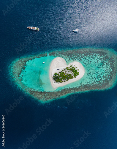 Drone Aerial view of beautiful tropical heart shaped island among blue sea water at Maldives paradise with yachts on panoramic background