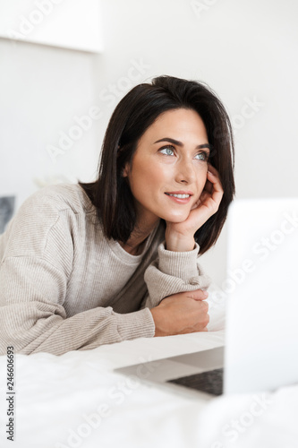 Leinwandbild Motiv Photo of caucasian woman 30s using laptop, while lying in bed with white linen in bright room