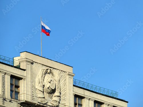Russian flag on the Parliament building in Moscow against blue sky. Facade of State Duma with soviet coat of arms, authority of Russia