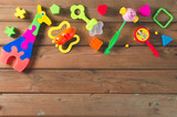 Top view or flat lay on colorful toys on dark wooden background with copy space.