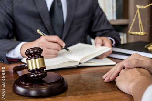 Judge gavel with scales of justice, Businesswoman and male lawyers or counselor discussing contract papers at law firm in office. Concepts of law - 246635843