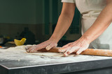 Female chef making dough with rolling pin - 246638685