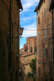 Fantastic view to the old narrow street, going down on Siena hills with bright blue sky and Basilica Cateriniana San Domenico on the background
