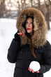 Beautiful young woman with very long red nails holding snowball in her hand. Snow all around her. Wearing worm fur hooded jacket. Blurred background.