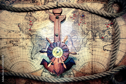 Old ship anchor,compass and rope. Travel and marine engraving background.Sea trip concept. World pirate map.Vintage and retro style.