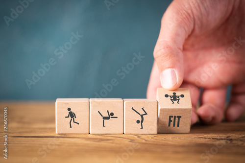 Icons on cubes symbolizing sports on wooden background - 246670045