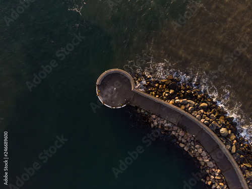 Pier at the entrance to the harbor in Helsingborg, Sweden during sunset from above.  © Viktor
