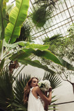 Young beautiful woman in white dress holding little bridal bouquet of flowers in hands dreamily looking in camera with big green leaves around while spending time in cozy greenhouse - 246695806