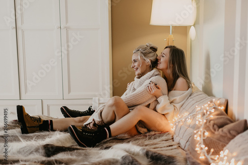Leinwandbild Motiv  beautiful girls in love cuddle in bed and laugh, the light from the garlands