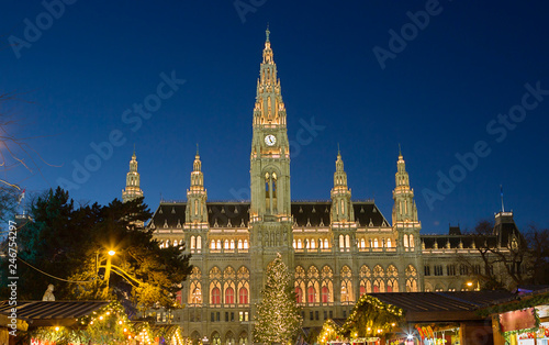 fototapeta na ścianę Vienna, Austria, town hall building in the evening. The building is built in the neo-Gothic style with a symmetrical main facade. The main facade of the town hall has 5 towers.