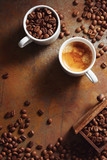 Cup of espresso with coffee beans scattered over a rustic surface.