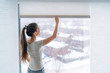 Leinwanddruck Bild Home blinds window shades woman opening shade blind during winter morning. Asian girl holding modern cordless top down luxury curtains indoors.