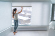 Leinwanddruck Bild Woman closing cellular shades on apartment window keeping energy and heat indoors with honeycomb blind curtain. Cordless pleated shades in modern home living lifestyle. Interior decor design.