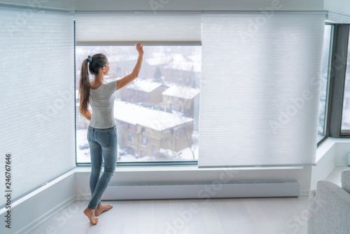Woman closing cellular shades on apartment window keeping energy and heat indoors with honeycomb blind curtain. Cordless pleated shades in modern home living lifestyle. Interior decor design.