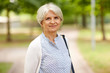 old age, retirement and people concept - portrait of happy senior woman at summer park