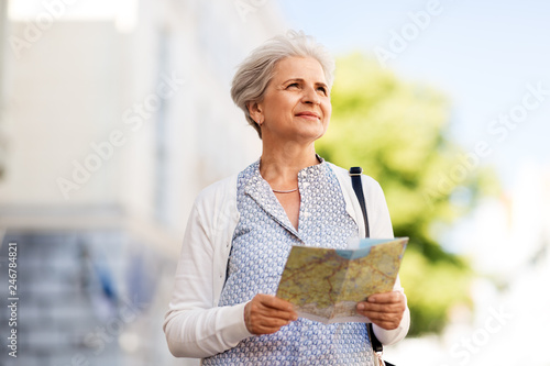 Foto Murales travel, tourism and retirement concept - senior woman or tourist with map on city street