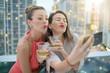 Leinwanddruck Bild - Two beautiful friends taking selfie on rooftop bar with city lights backdrop