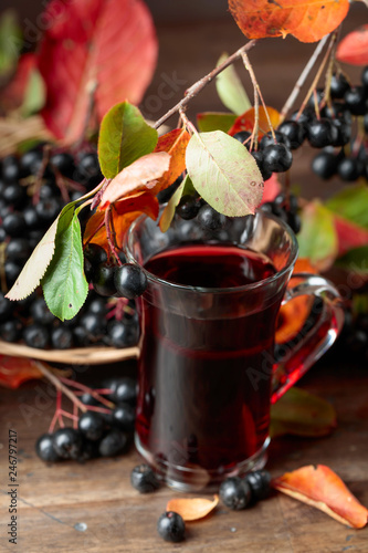 Fresh juice of ripe black chokeberry in glass and berries with leaves.