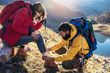 Leinwanddruck Bild - A woman has sprained her ankle while hiking, her friend uses the first aid kit to tend to the injury