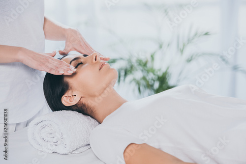 Leinwandbild Motiv cropped shot of young woman with closed eyes receiving reiki treatment on face