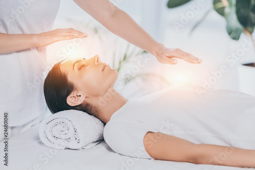 Leinwanddruck Bild cropped shot of reiki healer doing therapy session to calm young woman with closed eyes