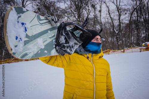 fototapeta na ścianę snowboarder in a mask holds a snowboard on his shoulder