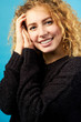 Portrait of young attractive smiling cheerful curly ginger girl dressed in black sweater.