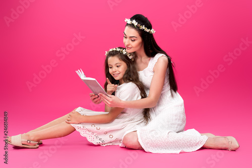 Leinwandbild Motiv beautiful happy mother and daughter in white dresses sitting and reading book together on pink