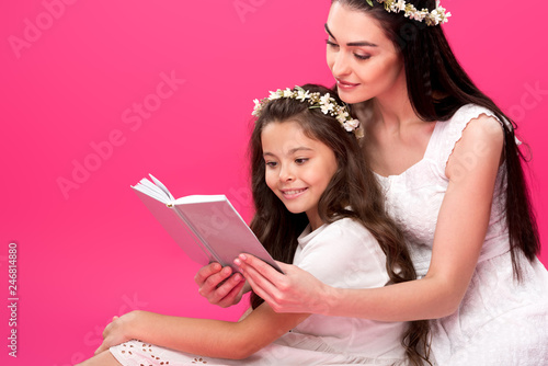 Leinwandbild Motiv beautiful mother and daughter in white dresses sitting together and reading book isolated on pink