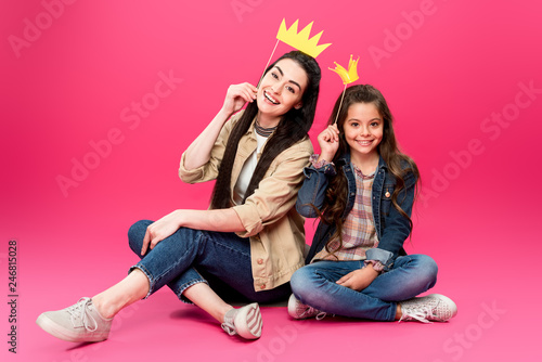 Leinwandbild Motiv happy mother and daughter holding crowns on party sticks and smiling at camera on pink