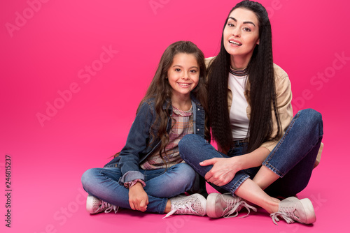 Leinwandbild Motiv full length view of beautiful happy mother and daughter sitting together and smiling at camera on pink