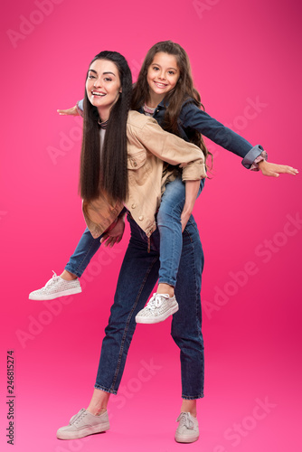 Leinwandbild Motiv full length view of beautiful happy mother and daughter piggybacking and smiling at camera isolated on pink