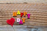 Happy day écrit en lettres bois et coeur rouge sur un fond bois