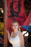 Young blonde woman staying near cuba flag and che Guevara