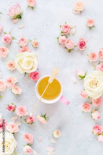 Tea cup with roses. Flat lay of rose flowers , petals and cup of tea over textured background - 246857296