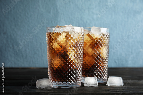 Leinwanddruck Bild Glasses of refreshing cola with ice cubes on table