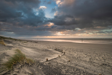 Stunning Winter sunrise over West Wittering beach in Sussex England with wind blowing sand across the beach © veneratio