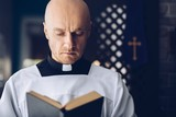Catholic priest reading bible in church.