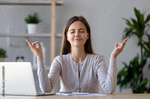 Calm young woman worker taking break doing yoga exercise at workplace, happy mindful female student meditating at home office desk feel balance harmony relaxation, stress relief zen at work concept - 246885811