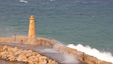 Storm in the Mediterranean sea, waves break on a stone harbor with a lighthouse in the city of Girne (Kyrenia), Turkish Republic of Northern Cyprus. - 246899440