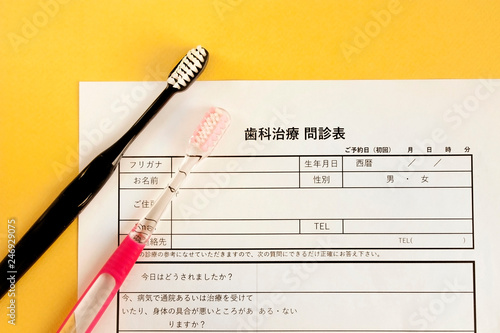 歯の治療の問診票と歯ブラシ、歯医者の予約 - 246929075