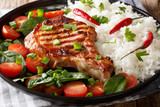 grilled pork chop cutlet with rice and fresh vegetable salad close-up on a plate. horizontal