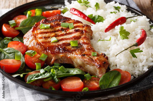 grilled pork chop cutlet with rice and fresh vegetable salad close-up on a plate. horizontal - 246934259