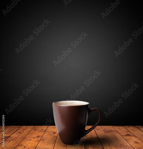 Leinwanddruck Bild Cup of drink on wooden table with dark background