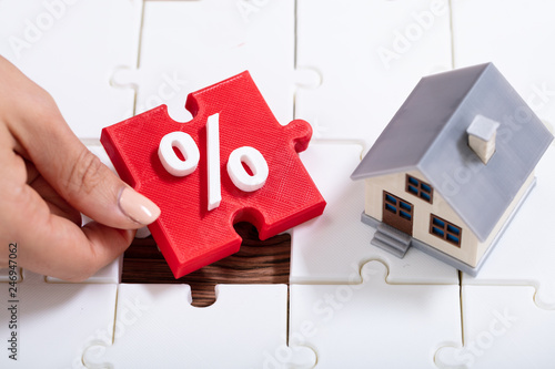 Leinwanddruck Bild Person Holding Percentage Puzzle Pieces Near The House Model